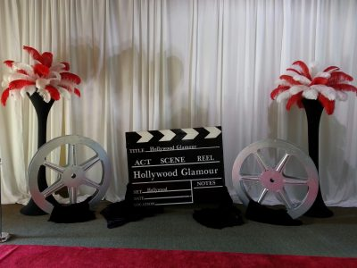 Clapperboard with Movie Reels and Feather Towers